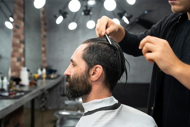 髪をとかす美容師を閉じる