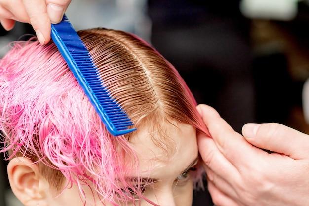 클로즈업 미용사 손에 헤어 살롱에서 빗으로 젊은 여자의 분홍색 머리카락을 분리하고 있습니다.