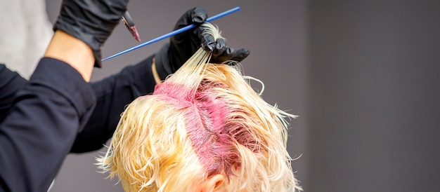 Close up of hairdresser's hands applying pink dye on woman's blonde hair at a hair salon