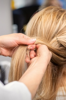 Close up of the hairdresser's hands braiding the client's hair in beauty salon