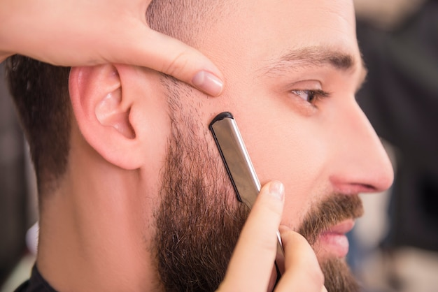 Close-up of hairdresser shaving an old-fashioned razor.