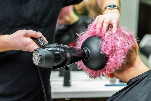 Close up of hairdressers hands drying short pink hair with blow dryer.