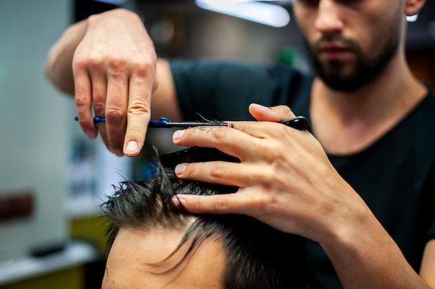 Close-up of hairstylist cutting customer hair