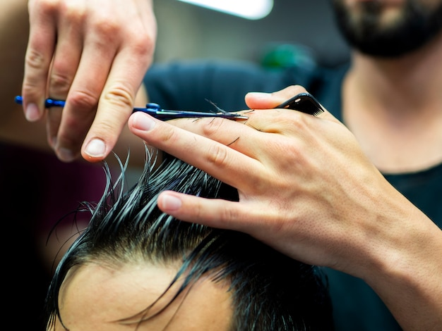 Close-up of hairstylist cutting hair