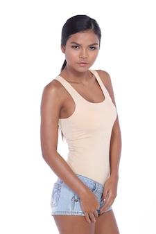 Закройте половину тела азиатской женщины 20-х годов с модными черными прямыми волосами, носящими бежевые обширные короткие джинсы. загорелая кожа девушки выражает сильные эмоции на белом фоне изолированы