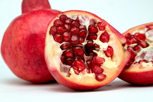 Close up of half-divided pomegranates in white background