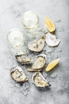 Close-up of half dozen of fresh opened oysters and shells with lemon wedges, two glasses of white wine or champagne, top view, grey rustic concrete background.