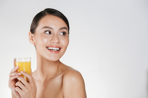 Close up of half-naked gentle woman with healthy fresh skin looking away and holding orange juice from transparent glass, isolated over white wall