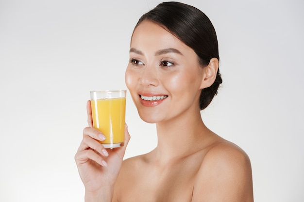 Close up of half-naked lady with healthy fresh skin and broad smile drinking orange juice from transparent glass, isolated over white wall