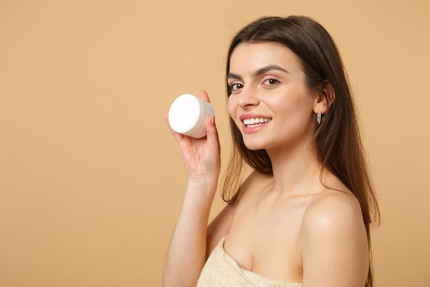 Close up half naked woman with perfect skin nude make up applying facial cream isolated on beige pastel wall