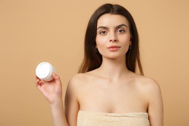 Крупным планом полуобнаженная женщина с идеальной кожей, обнаженная, наносит крем для лица, изолированную на бежевой пастельной стене Premium Фотографии
