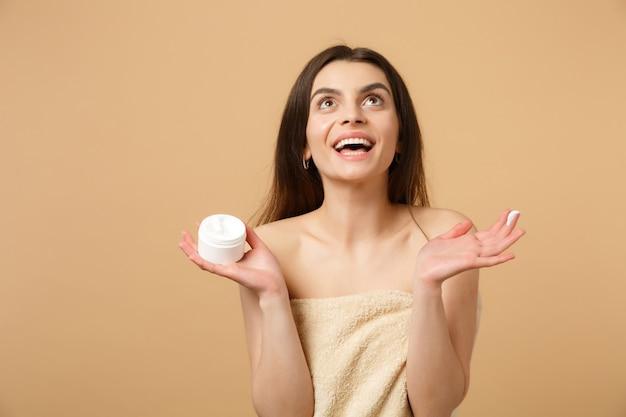 ベージュのパステルカラーの壁に分離されたフェイシャルクリームを適用して完璧な肌のヌードメイクで半分裸の女性を閉じます
