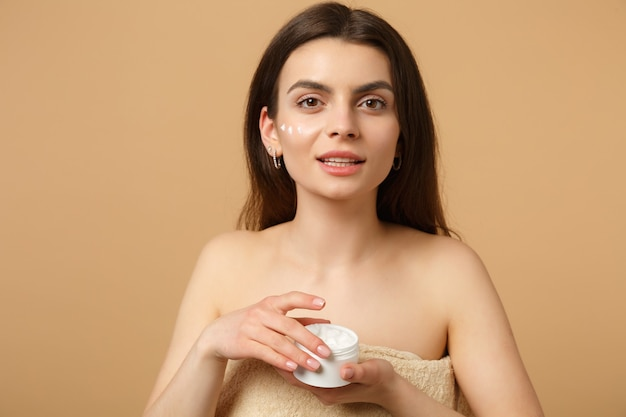 Крупным планом полуобнаженная женщина с идеальной кожей, обнаженная, наносит крем для лица, изолированную на бежевой пастельной стене