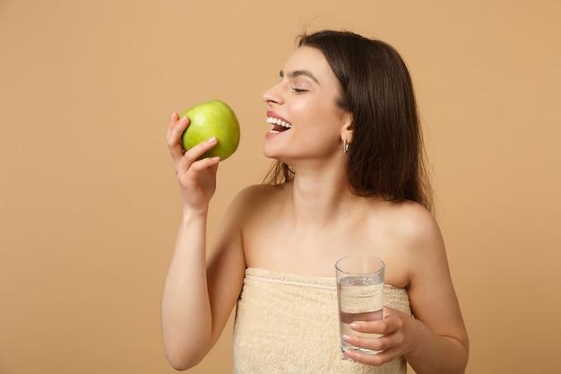 완벽한 피부를 가진 반 벌거 벗은 여자를 닫습니다, 누드 메이크업은 베이지 색 파스텔 벽에 고립 된 사과와 물을 보유하고 있습니다.