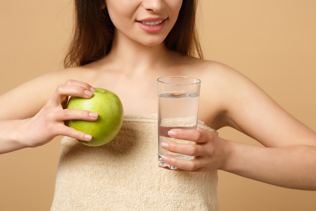 Close up half naked woman with perfect skin, nude make up holds apple and water isolated on beige pastel wall