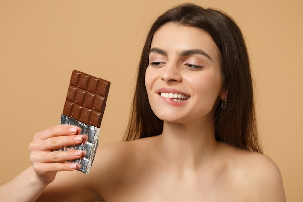Close up half naked woman with perfect skin, nude make up holds chocolate bar isolated on beige pastel wall