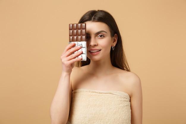 Primo piano donna mezza nuda con pelle perfetta, trucco nudo tiene una barretta di cioccolato isolata su muro beige pastello