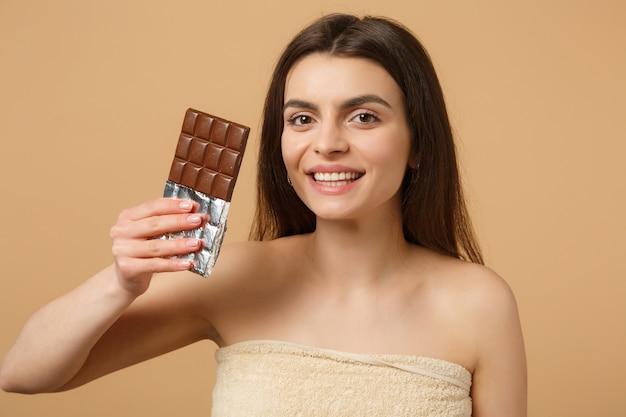 완벽한 피부를 가진 반 벌거 벗은 여자를 닫습니다, 누드 메이크업은 베이지 색 파스텔 벽에 고립 된 초콜릿 바를 보유하고 있습니다.