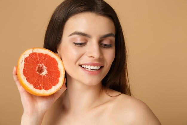Close up half naked woman with perfect skin nude make up holds grapefruit isolated on beige pastel wall