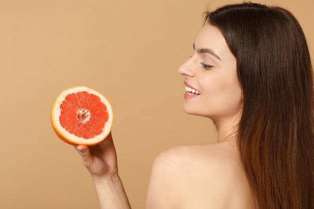 Крупным планом полуобнаженная женщина с идеальной кожей обнаженного макияжа держит грейпфрут на бежевой пастельной стене
