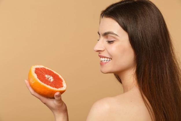 完璧な肌のヌードメイクで半分裸の女性を閉じるベージュのパステルカラーの壁に分離されたグレープフルーツを保持します