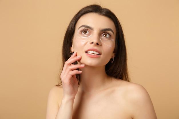 Primo piano donna mezza nuda con pelle perfetta, macchie di trucco nude sotto gli occhi isolate su muro beige pastello