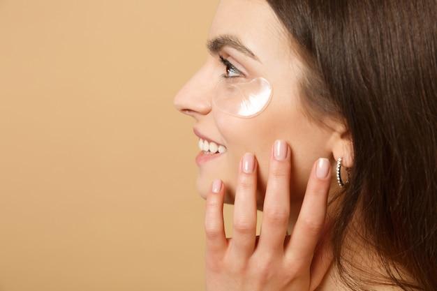 Крупным планом полуобнаженная женщина с идеальной кожей, обнаженные пятна макияжа под глазами, изолированные на бежевой пастельной стене