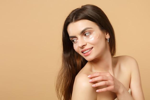 완벽한 피부를 가진 반 벌거 벗은 여자를 닫고, 베이지 색 파스텔 벽에 고립 된 눈 아래 누드 메이크업 패치