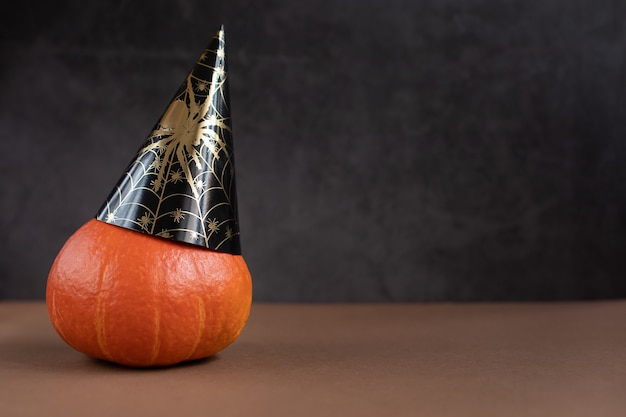 Close up of halloween pumpkin in a black paper cap with a spider on a dark background
