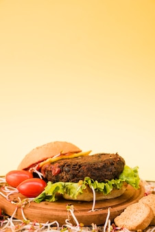 Close-up of hamburger with cheery tomatoes; bread and lettuce on yellow background