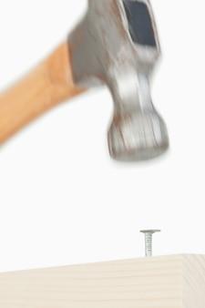Close up of a hammer driving a nail