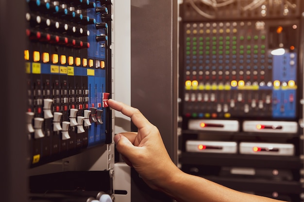Close-up hand adjust the volume on sound mixer in studio workplace.