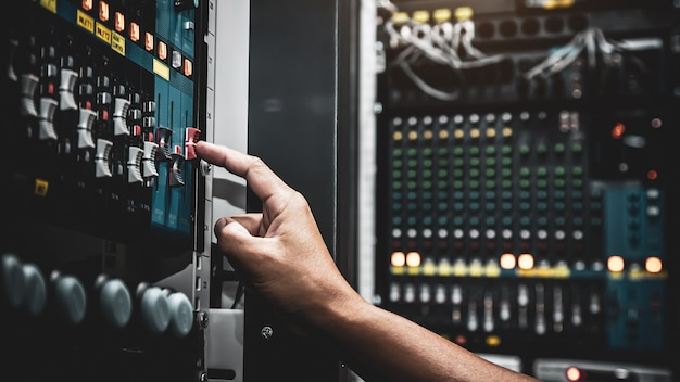 Close up hand adjust the volume on sound mixer in studio
