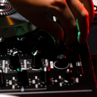 Close-up hand adjusting dj console