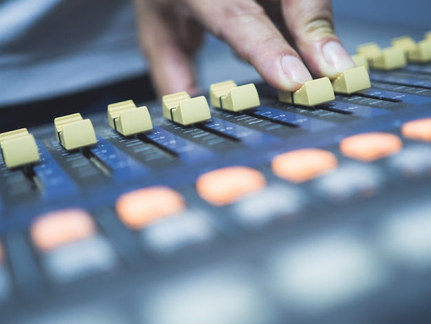 Close up of hand adjustment digital mixing console for recording studio