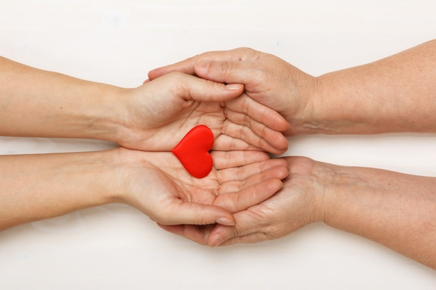 Close-up of the hand of an adult daughter and an older mother holding a heart together