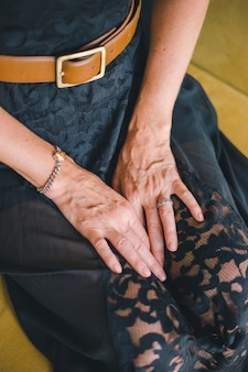 Close-up of the hand of an adult woman lying on her knees on a blurred background of a yellow sofa.