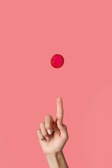손과 빨간 콘돔을 닫습니다