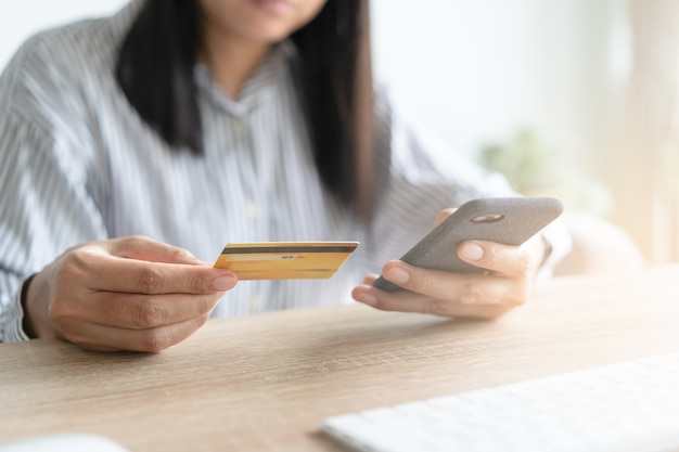 Close up hand of asian women are buying online with a credit card.