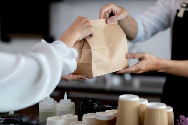 손을 닫습니다. 아시아 젊은이 또는 바텐더가 커피숍에서 고객에게 서비스를 제공합니다. 카페에서 커피를 만드는 것. 개념 판매 종이 가방과 커피. 포터필터가 있는 메이커 머신을 닫습니다.