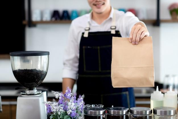 Закройте руку. азиатский молодой улыбающийся кассир, держащий бумажные пакеты, пока привлекательный бариста брюнет делает кофе в кафе. концепция продажи бумажный пакет и кофе.