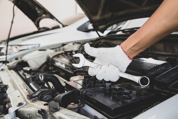 Close-up hand of auto mechanic is using wrench to repair a car engine