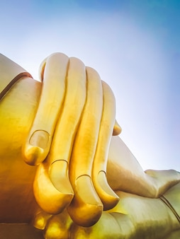 Close up hand of big buddha statue with blue sky at wat tha muang thailand. the most specifically iconic golden buddha statues