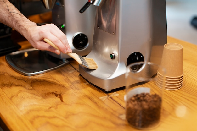 Close-up of hand brushing coffee machine