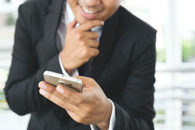Close up hand of business man using text mobile smart phone holding device and touching screen.