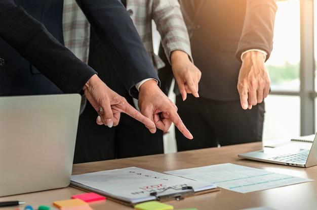 Крупным планом рука бизнес, указывая на бумажный годовой отчет на столе в офисе