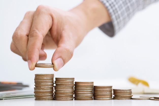 水差しのガラスにコインを入れて手で貯蓄お金のコインを積み上げた列で手のビジネスマンの会計計算機を閉じます
