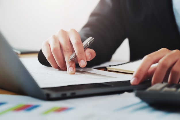 Close-up hand of businessman analyzing investment chart on paperwork with laptop in office.