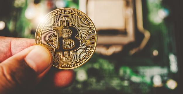 Close-up hand of a businessman holding a gold bitcoin