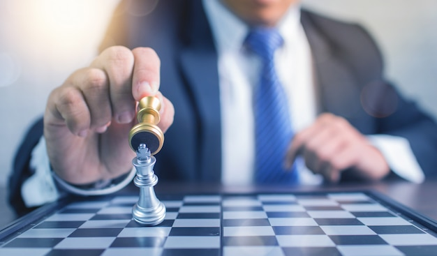 Close up hand of businessman playing chess and win in board game, strategy and planning business concept